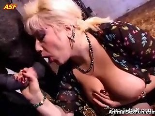 Blond-haired MILF deepthroats a horse's dick in a barn